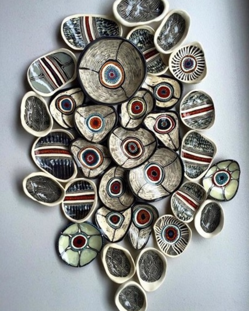 Cluster is a wall installation of Evans' earthenware ceramic dishes.Photo by Penny Evans