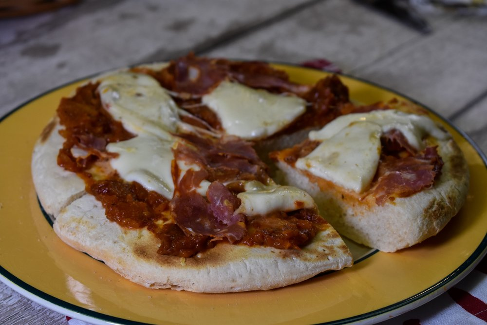 Our Pizza Base topped with homemade tomato sauce and mozzarella and salami