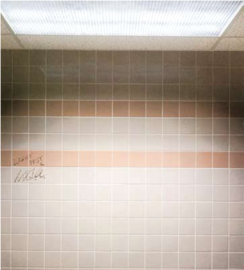 """This photo shows the dramatic visual improvement achieved simply by moving the overhead lighting just one ceiling panel (24"""") from the wall. The same irregularities in the tile are present, but the lighting makes them unnoticable."""