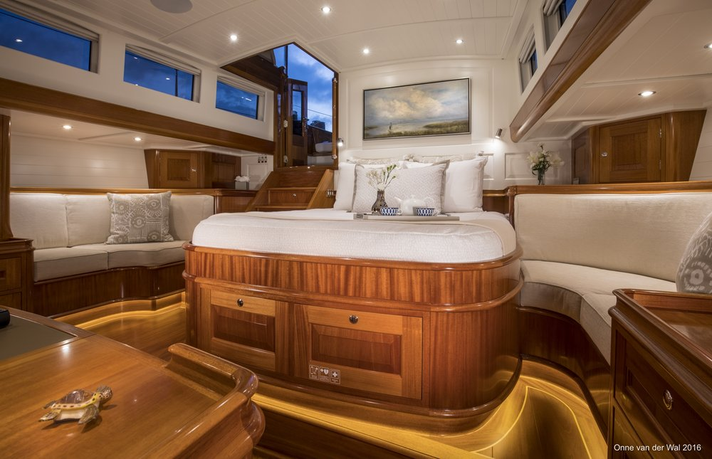 The master stateroom offers the yacht's hands-on owner easy access to the aft cockpit, where he can play an active role in sailing. Here and throughout the boat's interior, white-painted paneling is used strategically to keep the overall look from being too dark and heavy. Above the bed is a painting by Alabama artist Susan Downing-White that was commissioned by Waguespack to fit this space exactly and to evoke the owner's memories of fishing by casting nets.