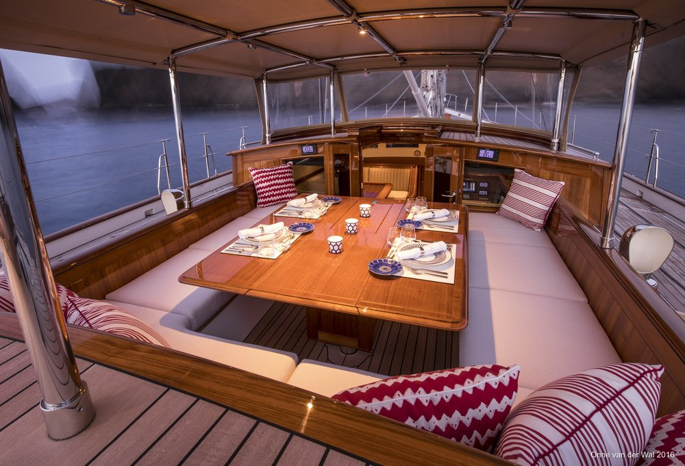 The dining table in the forward cockpit is set with Hermes china and Christofle silverware and surrounded by banquette seating. Red patterned pillows link this area visually with the distinctive red hue of the underwater ship, the area below the waterline on the yacht's aluminum hull.