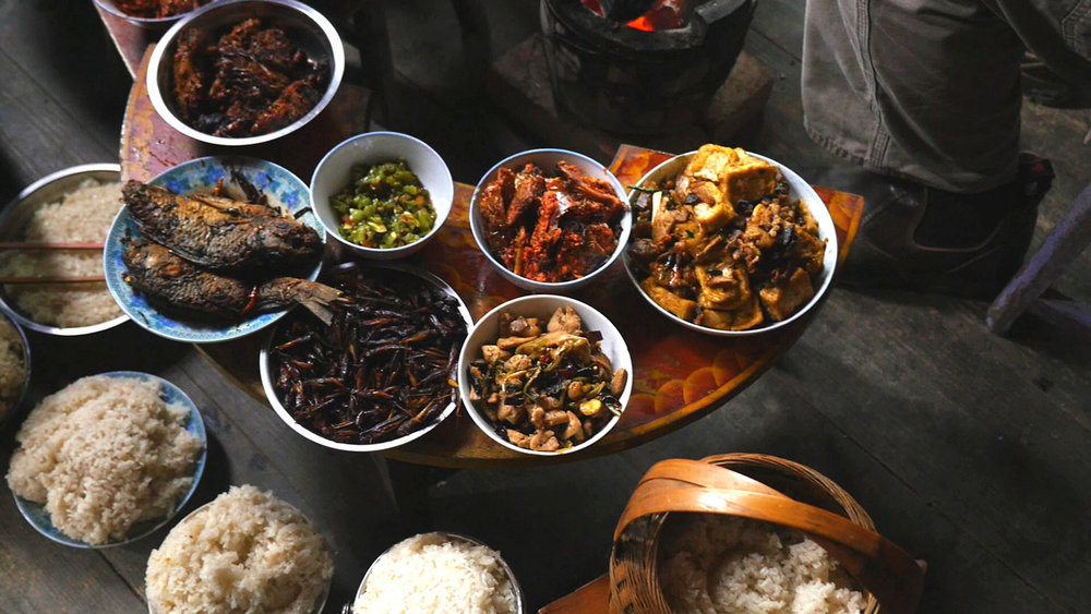 Dishes and baskets – laden with preserved fish, tofu, pork stir-fried with yam cakes, sticky rice and sautéed crickets – are balanced on the rims of the dishes around them or propped carefully on the floor surrounding the table.