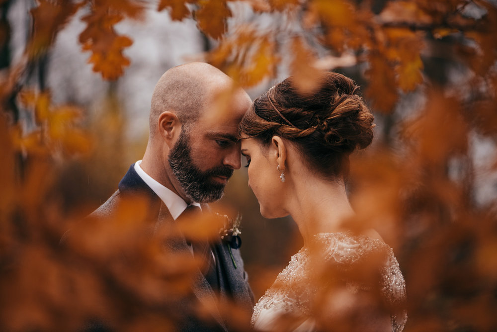 Wedding portrait through autumnal leaves