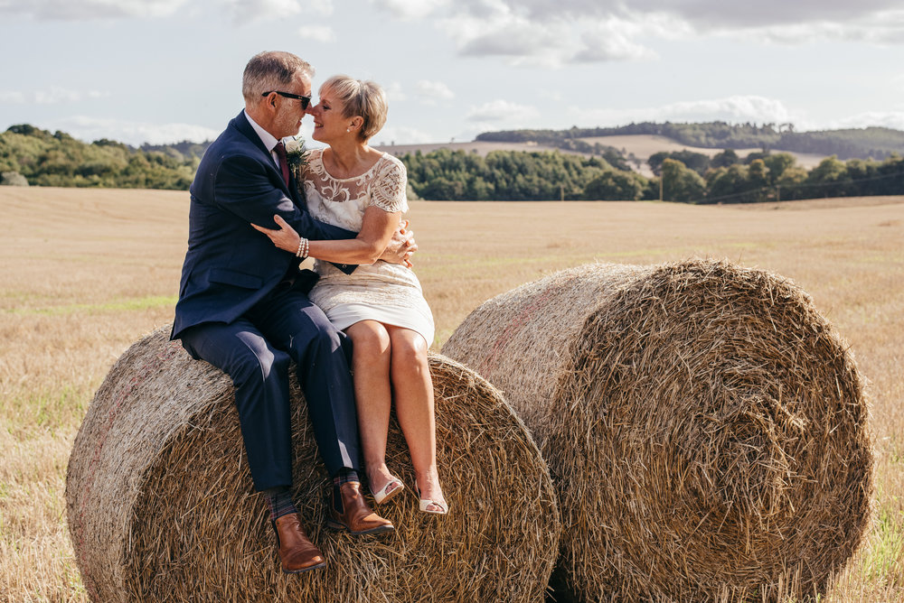 Bride and groom sat on hay bales