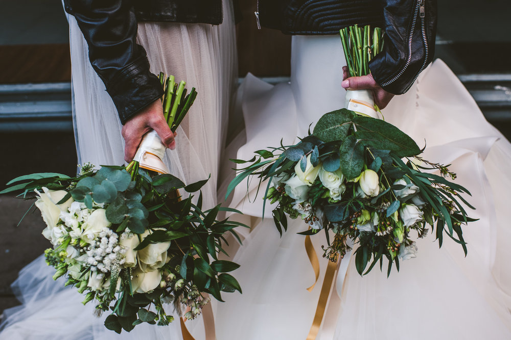 Same sex brides with wedding flowers
