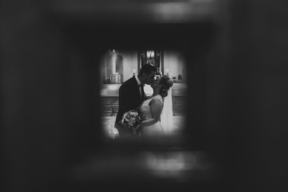 Creative wedding portrait through small window