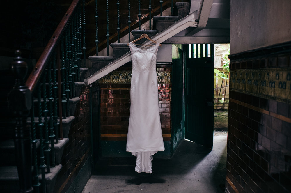 Wedding dress hanging in tenement close