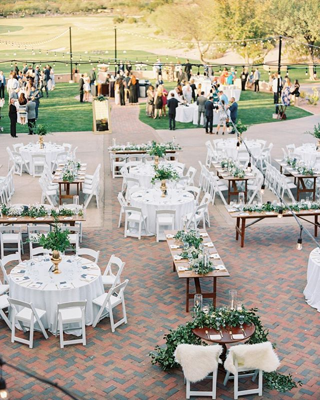 A full view of Kayle and Sam's reception set-up. Because of their guest count, the couple chose to mix rounds and rectangular tables. We love the variation of shapes and textures this creates in a reception space. . . . photo: @danielkimphoto  planning: @sassysoirees  venue: @superstitionmtngolfccweddings  farm tables: @tremaineranch