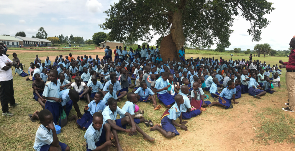 All of the students at Odek Primary School coming together after playing games and listening to our message in groups.