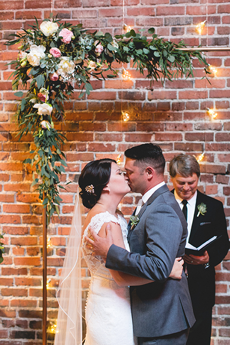 Bride and groom kissing in front of copper arch pipe with flowers