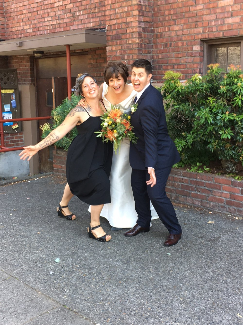 Excited wedding couple with guest and bouquet