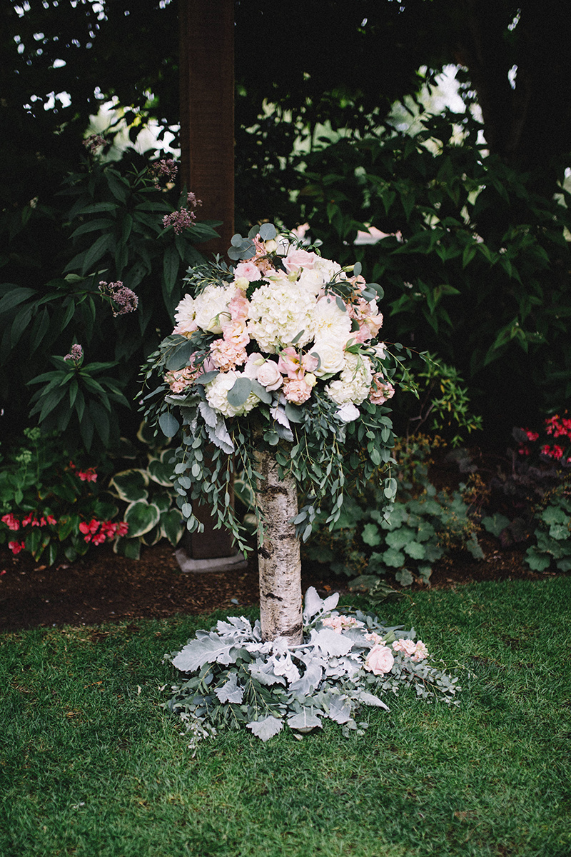 Wedding floral arrangement on a birch pedestal
