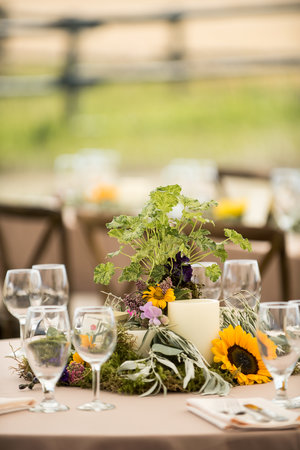 Wedding table floral arrangement with greens and sunflowers