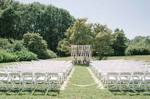 Ceremony design with copper pipe arch and flowers