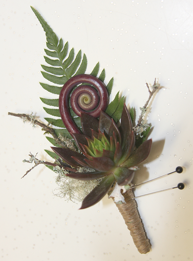 Floral boutonniere for wedding with succulent and fern
