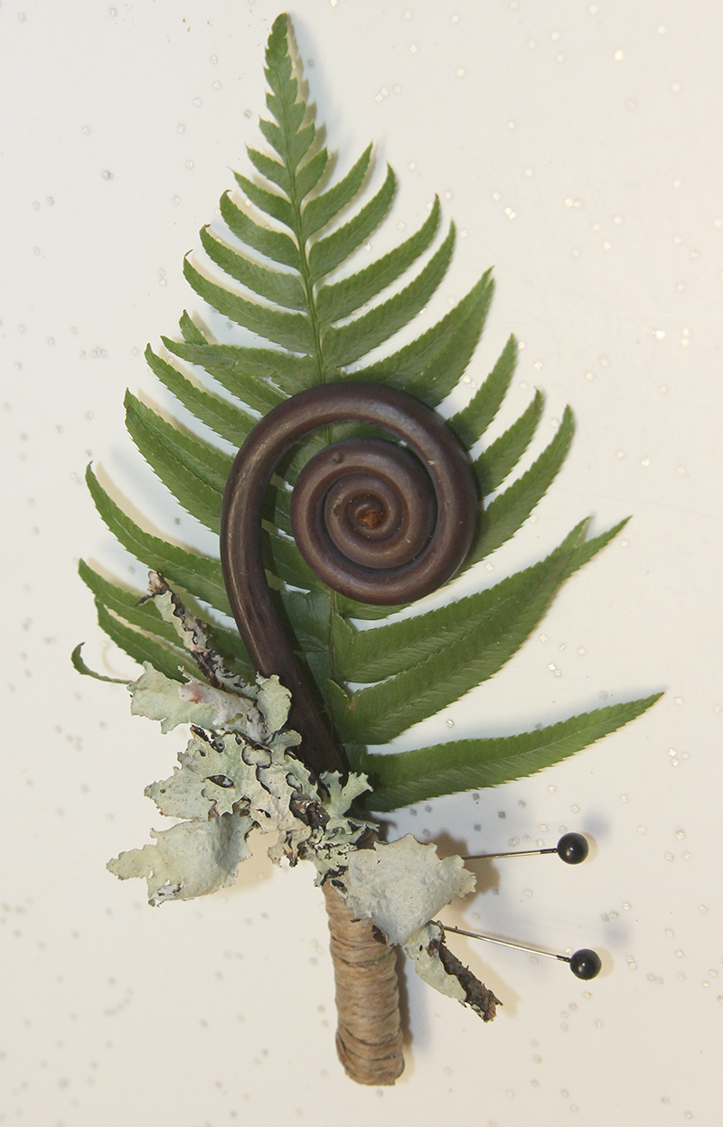 Floral boutonniere for wedding with ferns