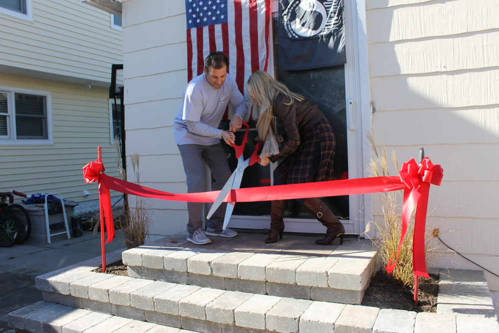 2014 Welcome Home recipients Leah Ottenbreit and Jacob Wolf make their new backyard official.