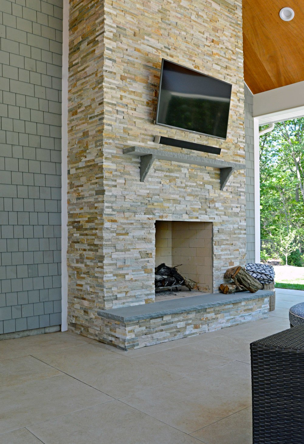 Custom outdoor fireplace with seating in Syosset, NY