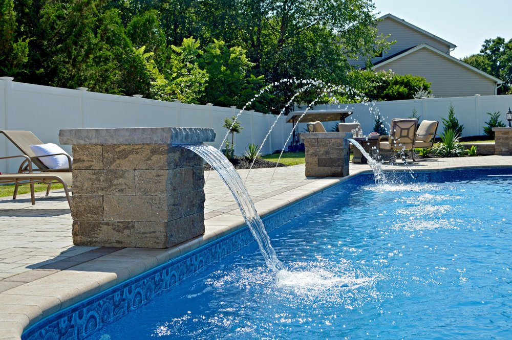 Brilliant landscape design with swimming pool and outdoor fireplace in Melville, New York
