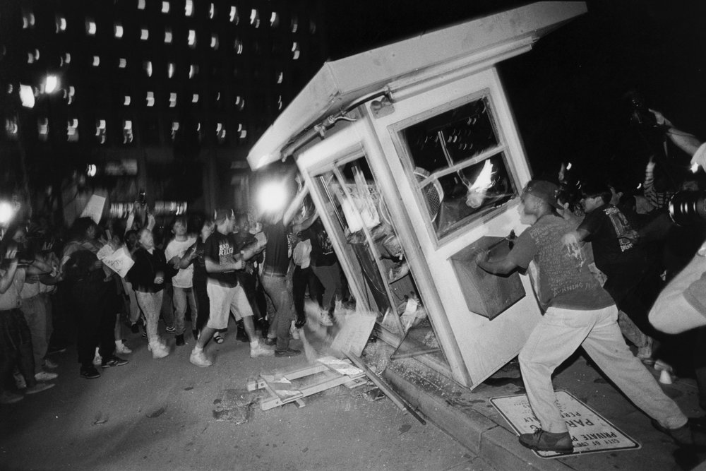 Rioters overturn a parking attendant booth at the LAPD Parker Center in downtown Los Angeles during the 1992 riots that swept the city for days after three of four police officers accused of the 1991 beating of Rodney King were cleared of all charges. The fourth officer was charged with use of excessive force. (Photo by Ted Soqui/Corbis via Getty Images)  Corbis via Getty Images