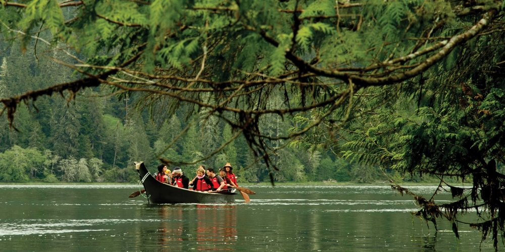 "Tashii Paddle School is a local First Nations (Tla-o-qui-aht) owned and operated business. We specialize in outdoor education including first national cultural interpretation, paddle instruction, and tours that explore a variety of areas in Tla-o-qui-aht Tribal Parks. We have been creating paddling opportunities for both tourists and the local community since 2012. Owners Tsimka and Emre bring their guiding and instructing experience from canoeing (Tsimka had previously guided canoe tours with her sister Gisele Martin's company Tla-ook), sea kayaking, and whitewater kayaking to the oldest and newest paddle sports on the west coast: Traditional Dugout Canoeing and Stand Up Paddle boarding, offering expert instruction, a truly unique paddling experience, and a source to the continued evolution of paddling on the west coast. Learn more about our paddling backgrounds by meeting our guides. ""T'ashii"" is a Tla-o-qui-aht word meaning path on land or on water. At T'ashii Paddle School our vision is to create a path to learning and connection with the natural environment through paddling. From March to October T'ashii Paddle School offers guided tours in a 25 foot hand carved dugout canoe (carved by Tsimka's father, Joe Martin). These tours are a window into local aboriginal culture and involve a walk through the old-growth rainforest showcasing 1000 year old red cedar trees. Year round, T'ashii Paddle School also offers daily stand up paddleboard (SUP) lessons and tours from calm ocean inlets, to open ocean touring, to paddle surfing. In addition, T'ashii Paddle Schools offers 2 day coastal stand up paddle boarding courses focused on specialized instruction and skill development. For locals looking for a chance to get out on the water, check out T'ashii's Locals SUP Program! Special events are posted on our facebook page. T'ashii Paddle School believes that sharing the ability to be on the water while having fun, exploring, and learning new skills is an experience that has a long lasting positive impact on anyone involved. Paddling is an amazing way to connect to the west coast, it's what we're passionate about and T'ashii Paddle School is our way of sharing our passion and continuing the progression of paddling on the west coast. We look forward to being out on the water with you!"