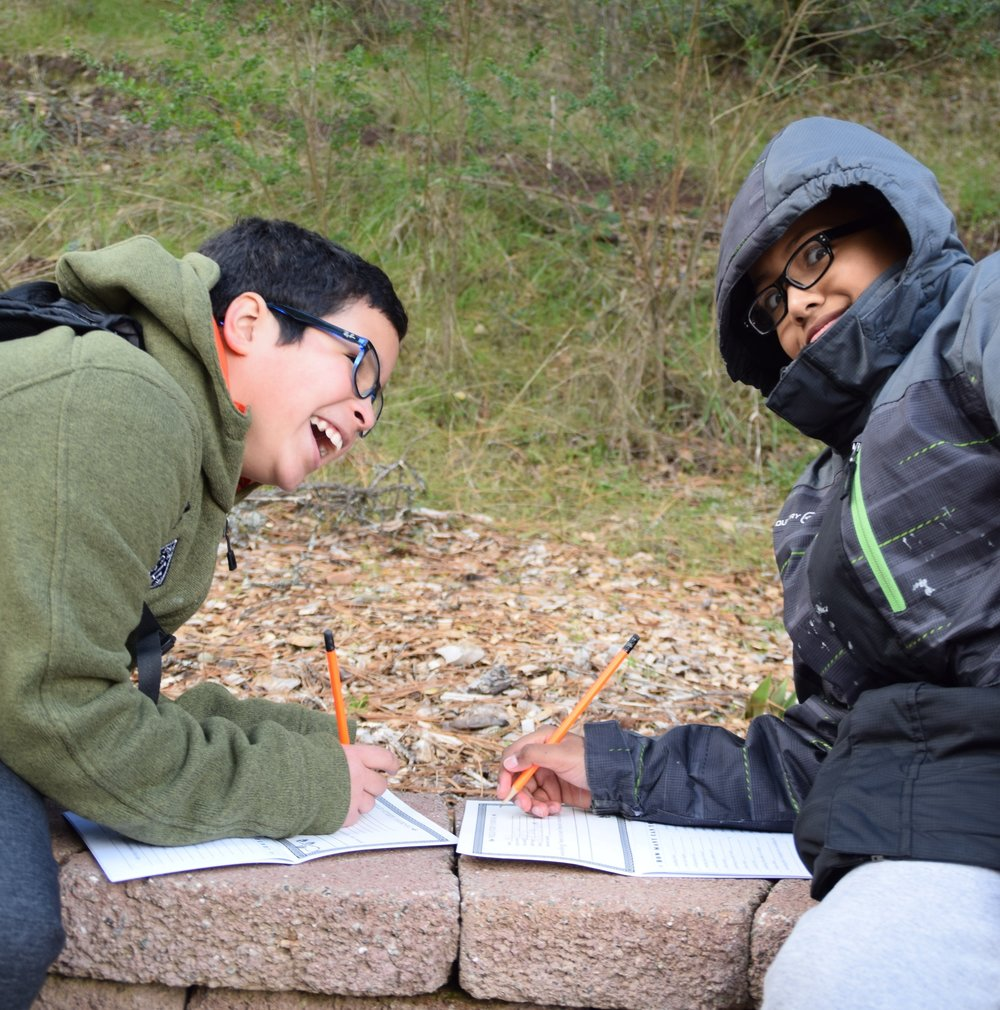 Laughing while learning outdoors, students from Si Se Puede, one of Rocketship Education's San Jose charter schools, enter information into their WOLF School journals.