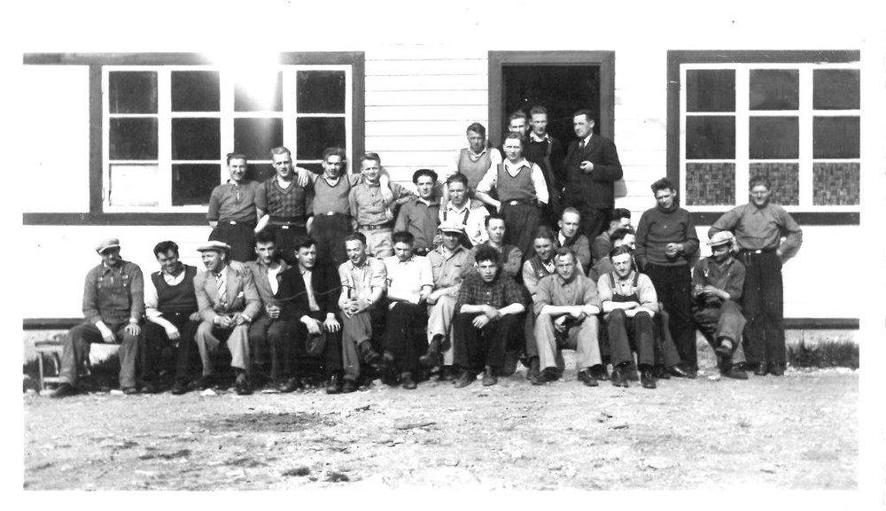 Grundere og sambygdinger som utgjorde arbeidsgjengen i oppstarten i 1940. Lars Karl Hjelle står til høyre i døråpningen, med pipe i hånden.