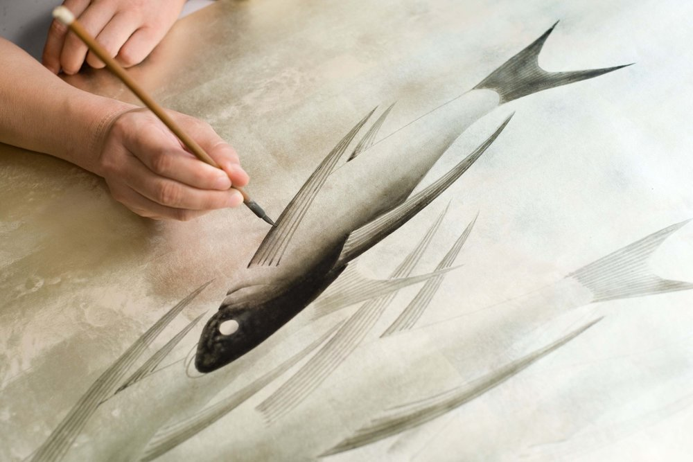 Artist hand painting fishes.