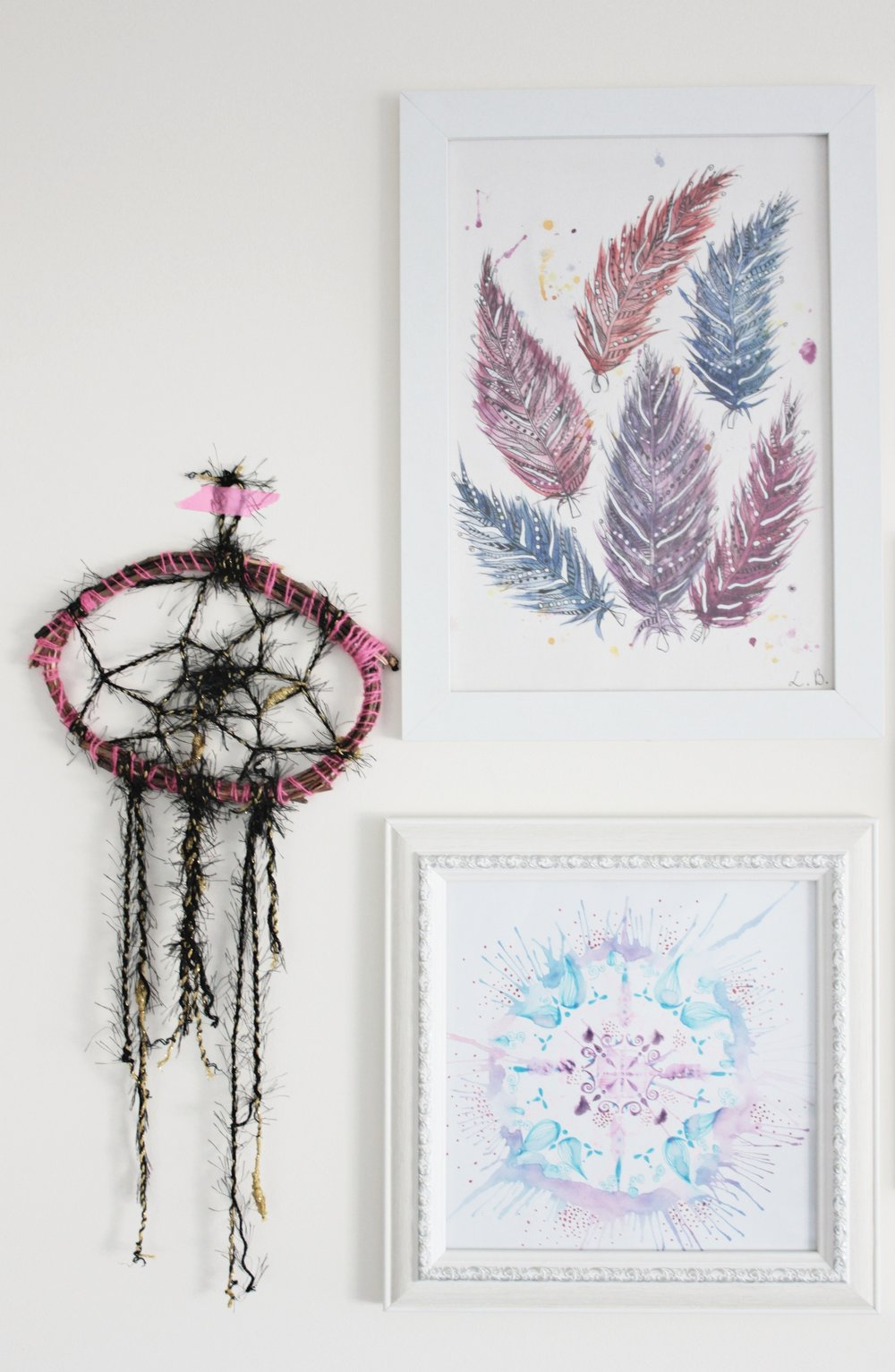 A dream catcher and framed artworks as a wall decoration idea