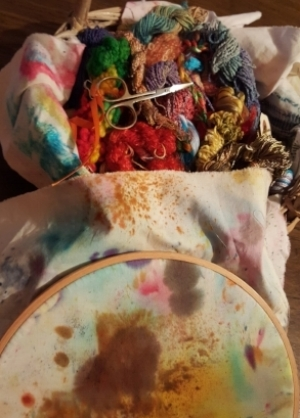 Basket of mostly hand dyed threads and hooped back ground fabric which is a dye clean-up rag.