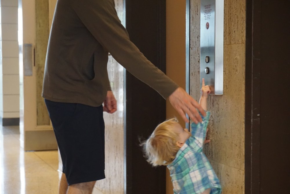 "With a little help from Dad, Leo pushes the ""UP"" button to call the elevator."