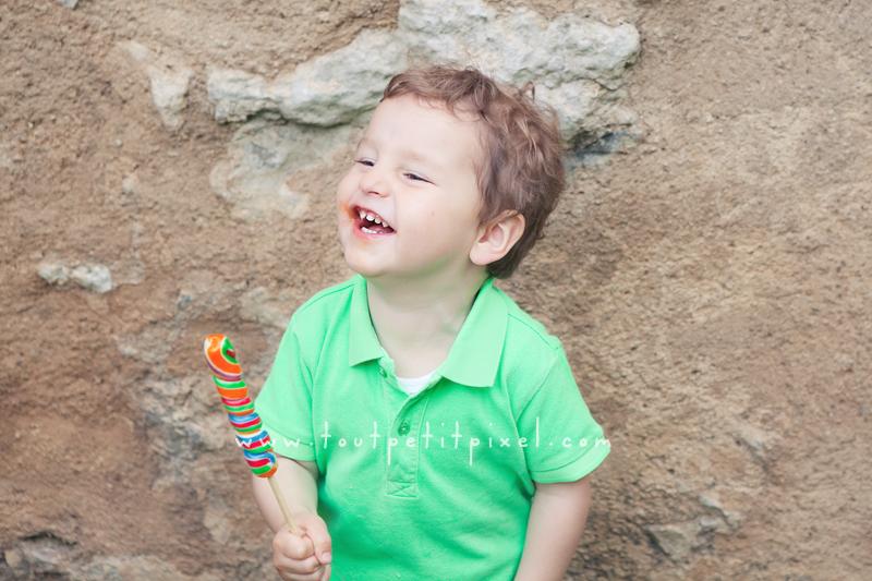 Enfant qui rit avec une sucette colorée à la main