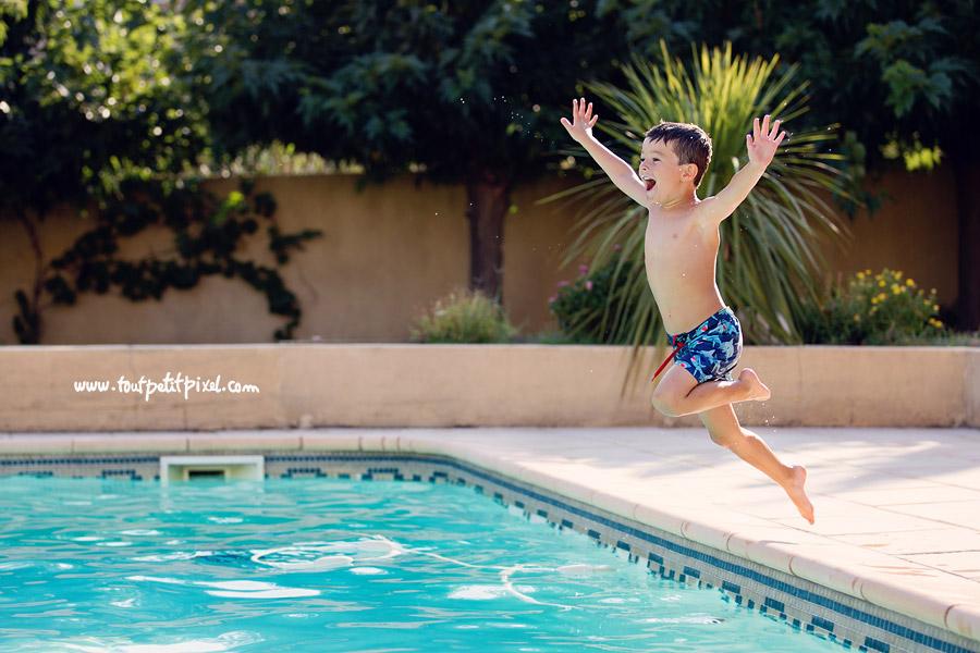Garçon qui saute dans la piscine