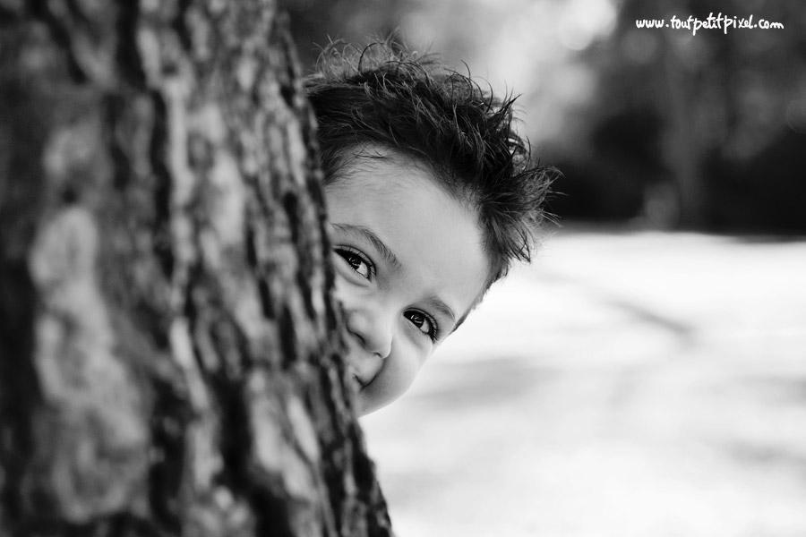 enfant qui se cache derrière un arbre