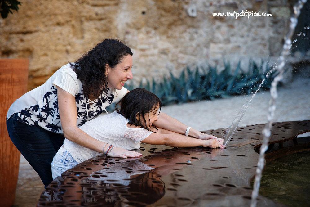 une-mere-et-sa-fille-jouent-avec-eau-fontaine.jpg
