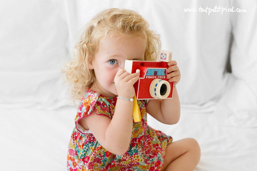 petite-fille-qui-tient-un-appareil-photo-jouet.jpg