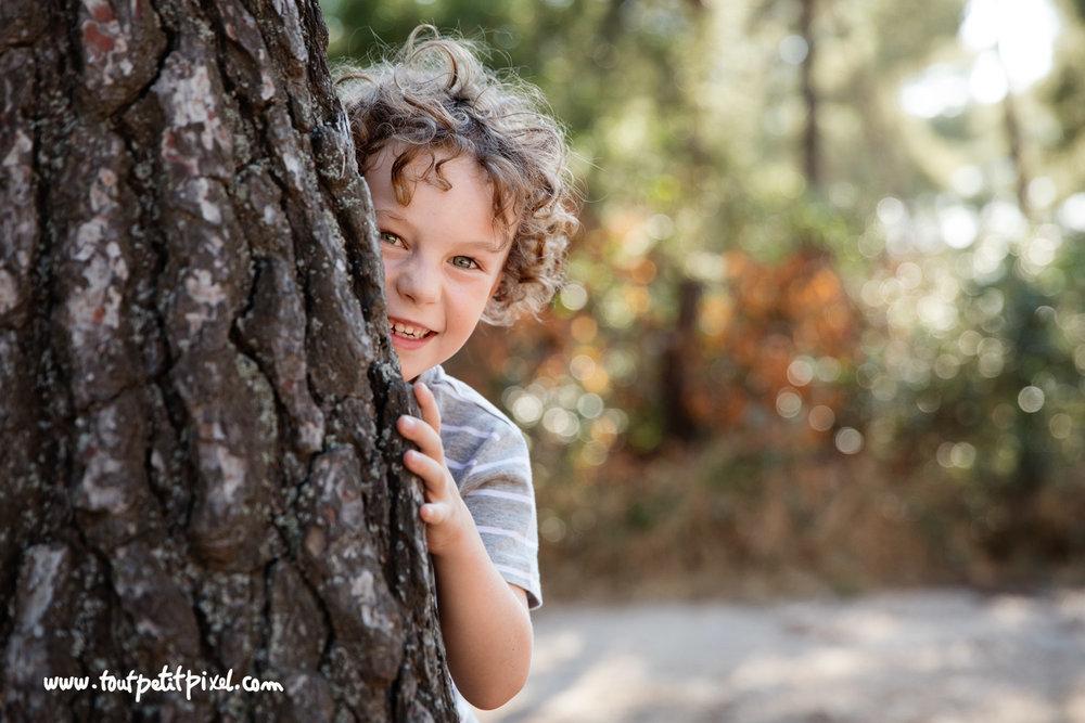 Enfant-qui-joue-a-cache-cache-derriere-un-arbre.jpg