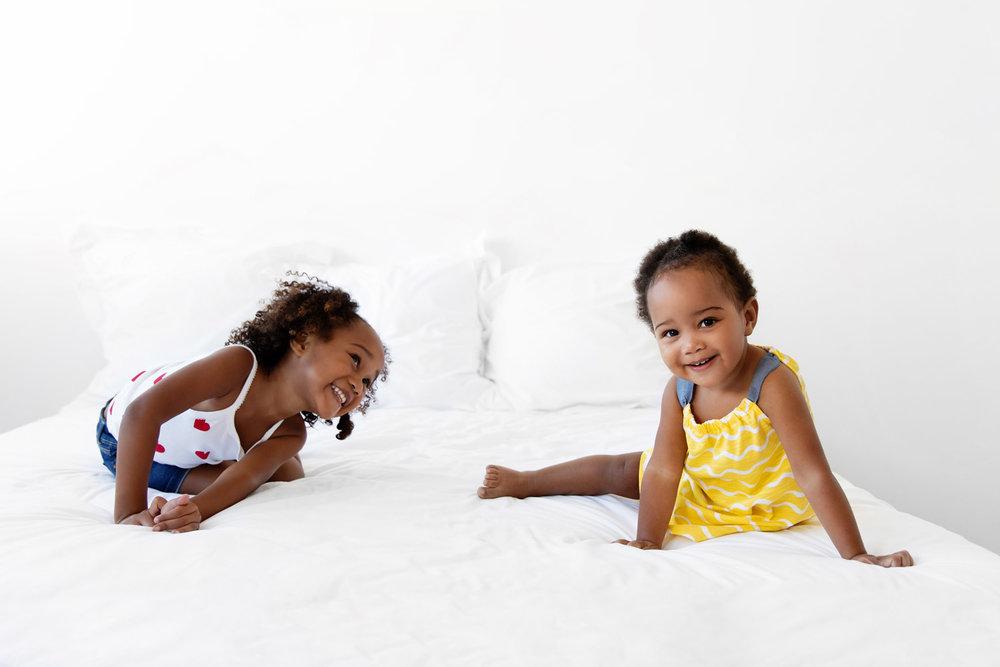 Deux petites filles qui rigolent sur un lit blanc par Tout Petit Pixel, photographe enfants à Marseille