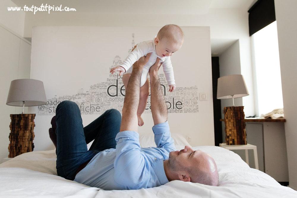 Papa qui fait voler son bébé dans les airs sur un lit par Tout Petit Pixel, photographe famille Marseille