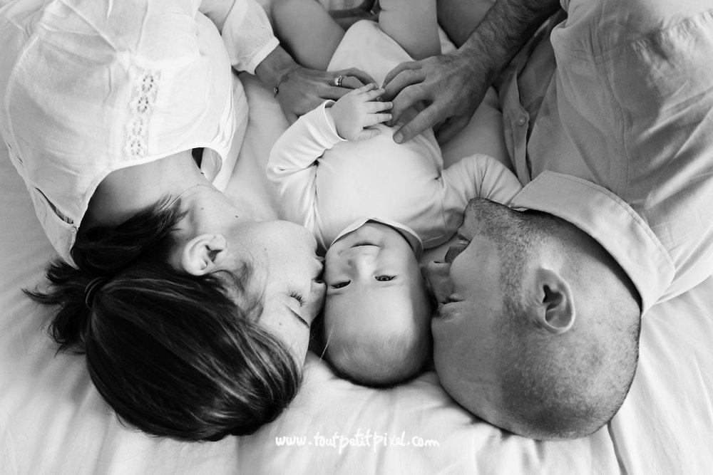Parents qui calinent leur bébé sur un lit par Tout Petit Pixel, photographe famille Marseille