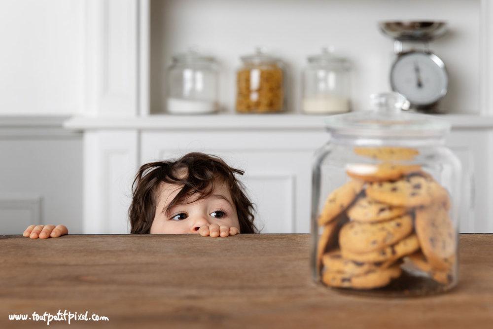 Jeune enfant qui regarde des cookies avec gourmandise par Tout Petit Pixel, photographe enfant à Marseile