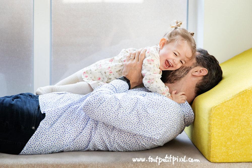 Petite fille qui rit pendant que son père l'embrasse dans le cou par Tout Petit Pixel photographe enfant lifestyle à Marseille