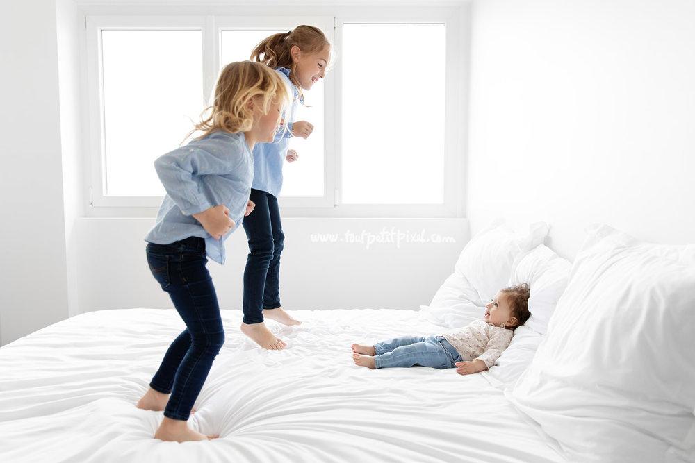 Petites filles qui sautent sur le lit devant un bébé qui les regarde en riant par Tout Petit Pixel, photographe enfants à Marseille