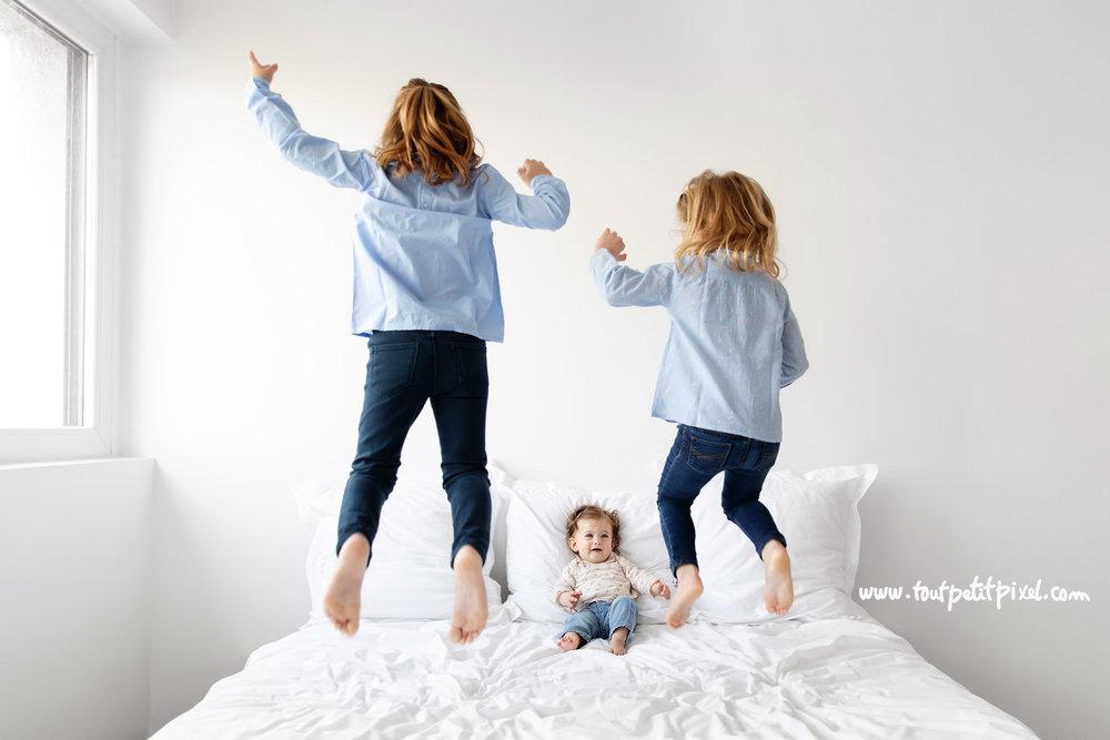 Grandes soeurs qui sautent sur un lit devant leur petite soeur qui les regarde en souriant par Tout Petit Pixel, photographe enfants à Marseille