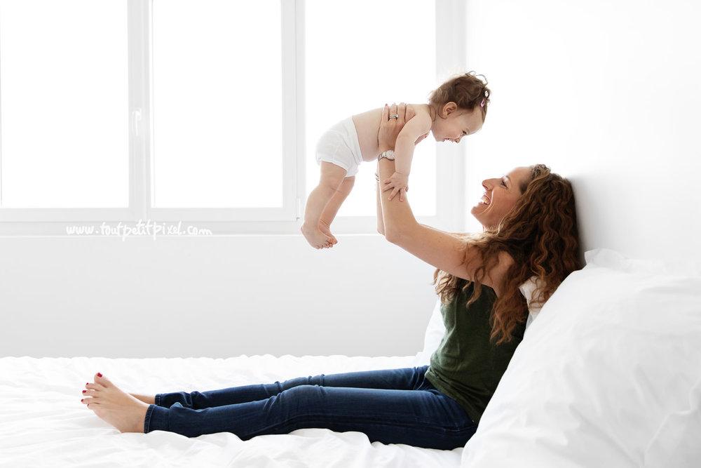 Maman qui fait voler son bébé dans les airs en souriant par Tout Petit Pixel, photographe bébé et famille à Marseille