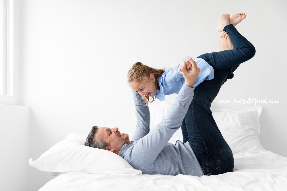 père et fille qui jouent sur le lit en riant par Tout Petit Pixel, photographe enfant et famille à Marseille