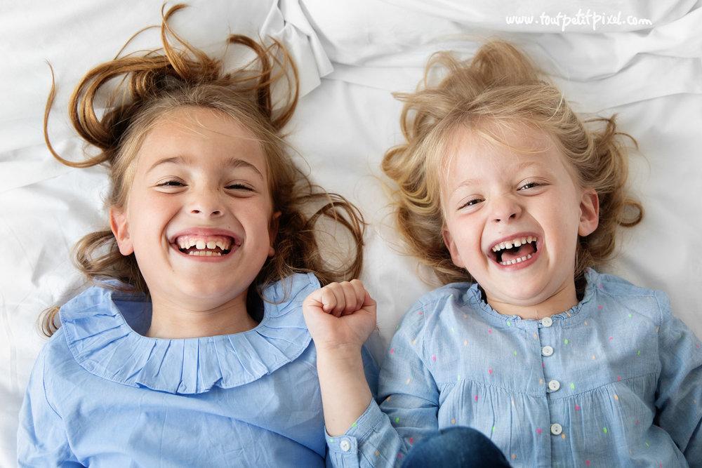 Deux petites filles qui rient ensemble sur un lit par Tout Petit Pixel, photographe enfants à Marseille