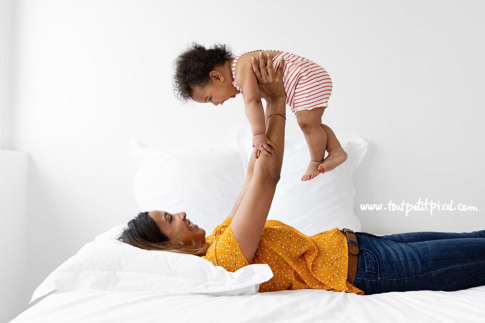 Maman et bébé qui jouent sur un lit par Tout Petit Pixel, photographe enfant Marseille