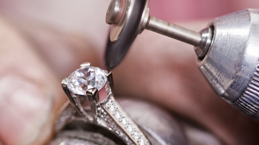 A Master Jeweler preparing to retip the prongs of an engagement ring.