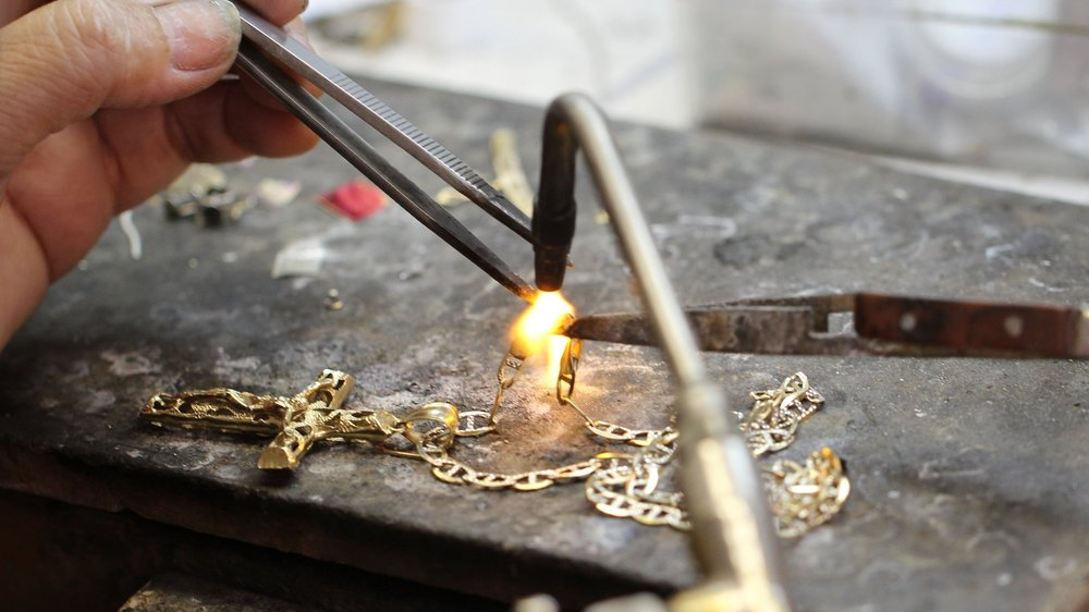 A Master Jeweler soldering the links of a customers broken yellow gold chain.